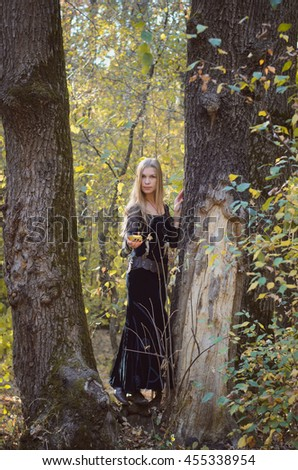 Young girl in a long fantasy black dress posing in an autumn forest