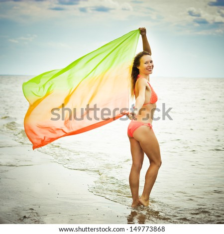 Young girl in a pareo arms to the side on the beach. - stock photo