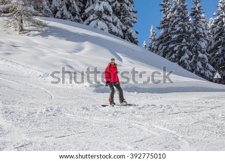 Young girl in a pink jacket snowboarding down the Alps in Switzerland. - stock photo