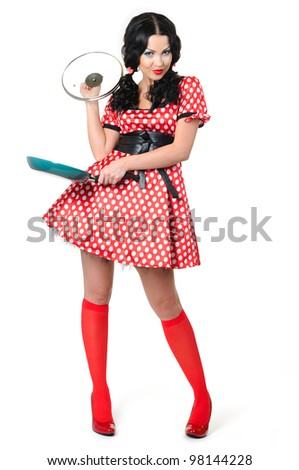 Young girl in a polka dot with frying pan on white background, pinup concept - stock photo