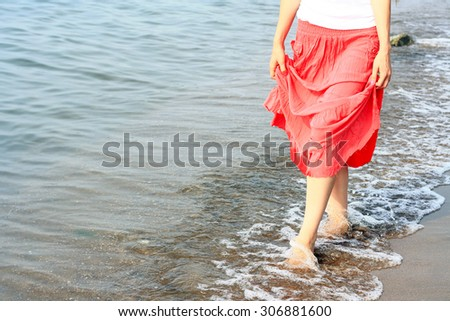 Young girl in a red dress goes barefoot on the coast in the summer sunny day.