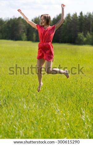 Young girl in a red dress jumping in a field on a sunny day - stock photo