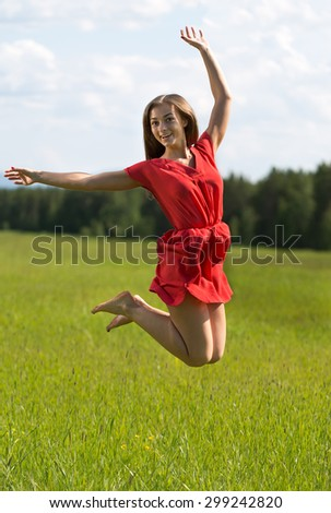 Young girl in a red dress jumping in a field with coniferous forest. - stock photo