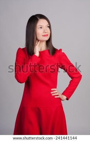 Young girl in a red dress on a grey background. Fashion photo of young beautiful woman with short hair.
