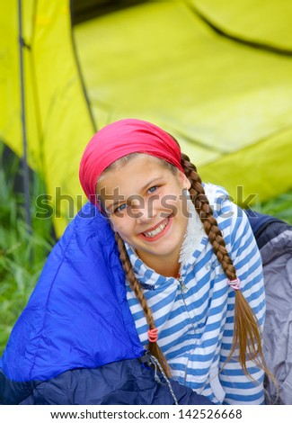 Young girl in a sleeping bag near tent in camping on the nature - stock photo