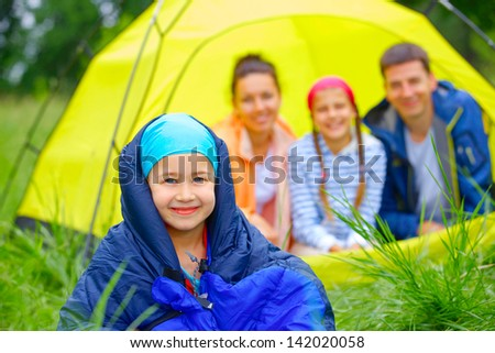 Young girl in a sleeping bag with her family near tent in camping on the nature - stock photo