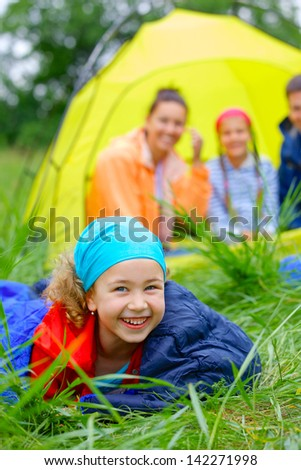 Young girl in a sleeping bag with her family near tent in camping on the nature. Vertical view - stock photo