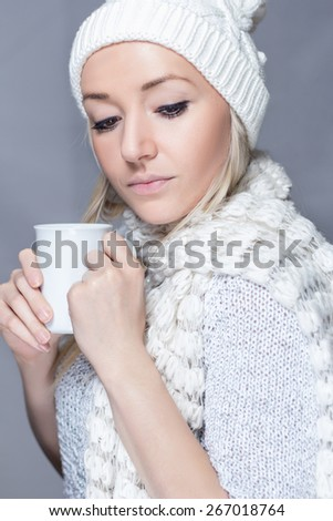 Young girl in a sweater with a white scarf and hat is holding a white cup  - stock photo