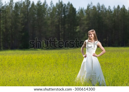 young girl in a wedding dress smiling in the field. - stock photo