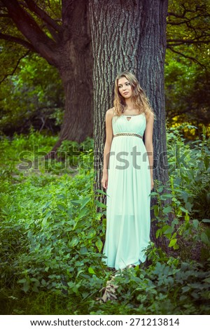 Young girl in a white dress in forest - stock photo