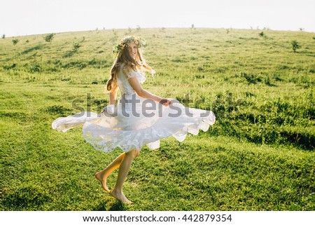 Young girl in a white dress in the meadow. Woman in a beautiful long dress posing on a meadow. Stunning bride in a wedding dress - stock photo