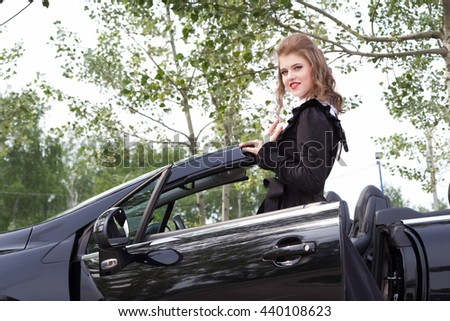 Young girl in an ancient dress next to a modern car