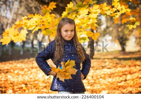 young girl in autumn park golden leaves