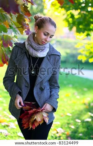 Young girl in autumn park holding red leaves