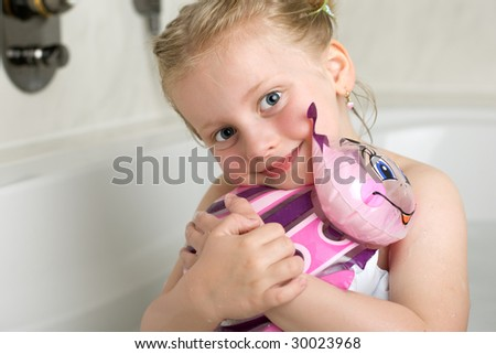 Young girl in bath tub with toy - stock photo