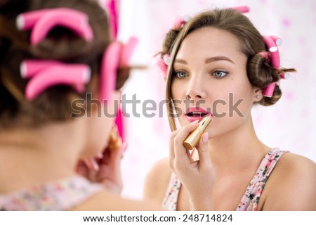 young girl in bathroom  applying lipstick and doing her make up ready - stock photo