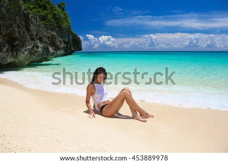 Young girl in bikini having fun on a tropical beach. Blue sea in the background. Summer vacation concept.