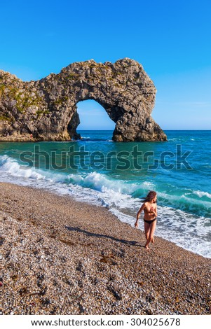 young girl in bikini playing at the beach near the famous Durdle Door in Dorset, England - stock photo