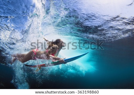 Young girl in bikini - surfer with surf board dive underwater with fun under big ocean wave. Family lifestyle, people water sport lessons and beach swimming activity on summer vacation with child - stock photo