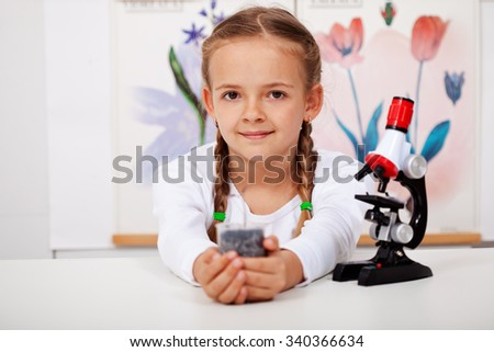 Young girl in biology class holding seedling - stock photo