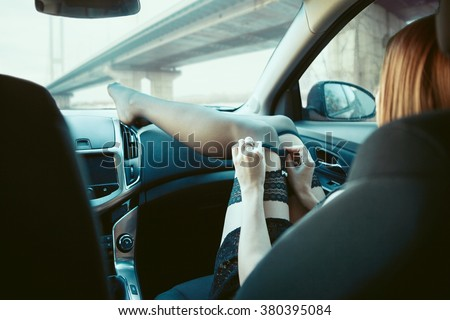 Young girl in black stockings in the car.