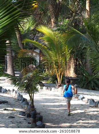 Young girl in blue running on a tropical island - stock photo
