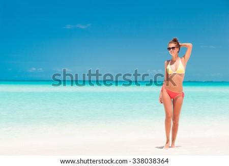 young girl in bright bikini walking at tropical beach - stock photo