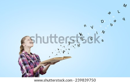 Young girl in casual holding book in hands - stock photo