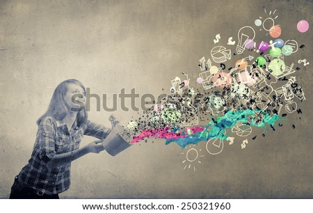 Young girl in casual splashing colorful paint from bucket
