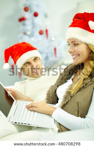 Young girl in Christmas hat using computer by her boyfriend