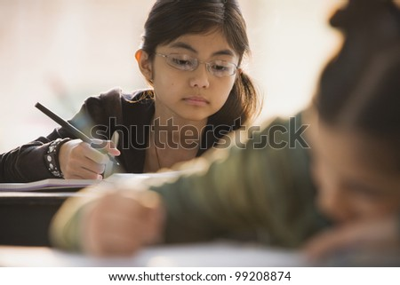 Young girl in classroom doing school work - stock photo