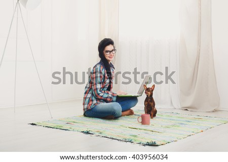 Young girl in computer glasses on a carpet with laptop and dog chihuahua. Hipster freelancer woman works at home. Home office, freelance. Brunette with laptop in modern interior. Soft tone, high key. - stock photo