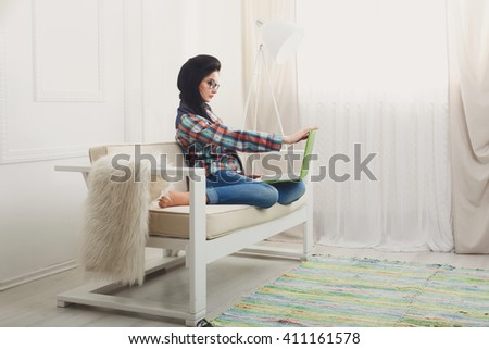 Young girl in computer glasses on a white sofa with laptop. Hipster freelancer woman works at home. Home office, freelance. Brunette with laptop in modern interior at white couch. Soft tone, high key. - stock photo