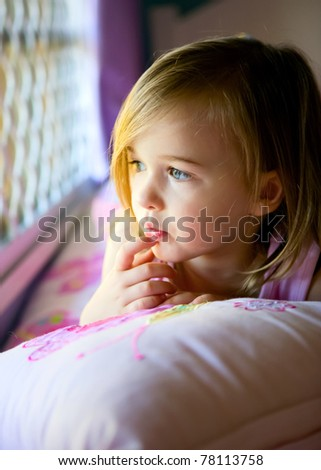Young Girl in contemplation on her bed looking out her bedroom window