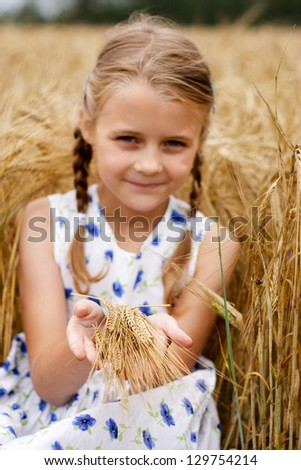 Young girl in country at cornfield. Focus on hands.