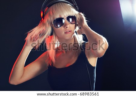 Young girl in dark in expression listening music - stock photo