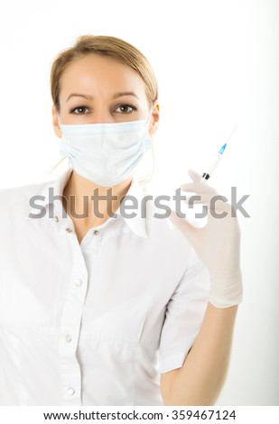 young girl in doctor bathrobe and rubber gloves holding a syringe - stock photo