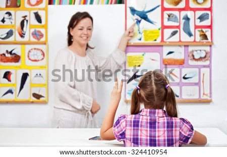 Young girl in elementary science class raising hand to answer teacher - stock photo