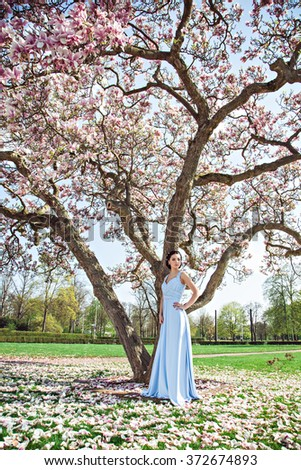 Young girl in evening dress with magnolia tree