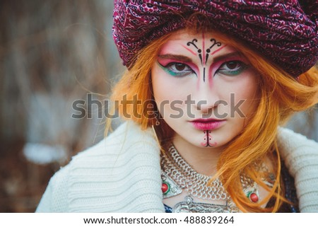 Young girl in extravagant style of ethnic grunge standing in autumn park