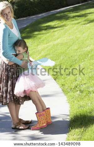 Young girl in fairy costume embracing mother on path at park - stock photo