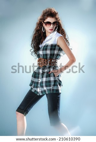 young girl in fashion dress wearing sunglasses in light background - stock photo