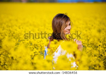 Young girl in field of flowers from back. - stock photo
