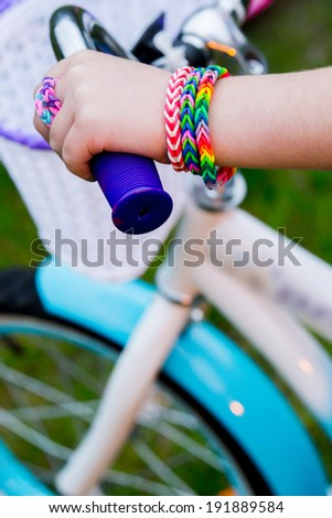 Young girl in flip-flops wearing loom bracelets on her hands and legs riding the bicycle. Close up. Young fashion concept