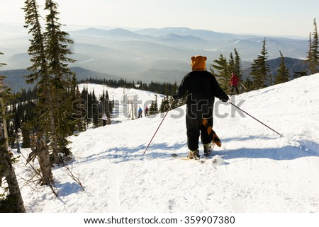 young girl in funny costumes skiing on a mountain - stock photo
