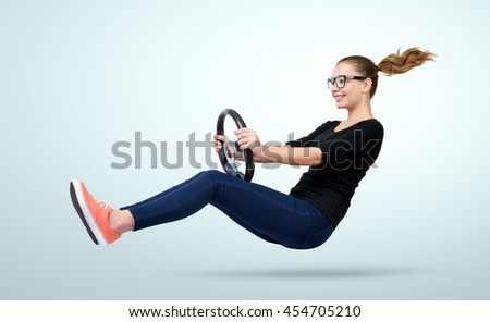 Young girl in glasses driver car with a wheel on background