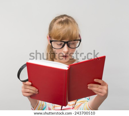 young girl in glasses looking at a book with lens - stock photo