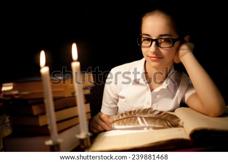 Young girl in glasses over book in dark with candles