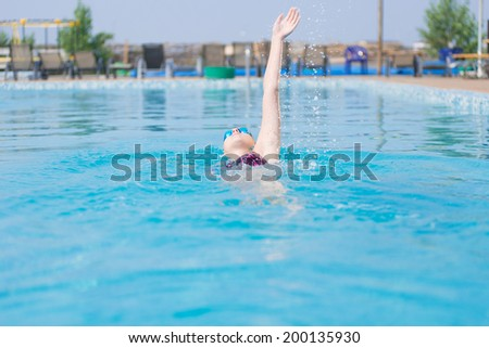 Young girl in goggles and cap swimming back crawl stroke style in the blue water pool