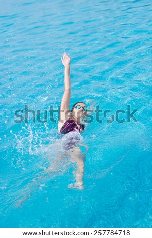 Young girl in goggles and cap swimming back crawl stroke style in the blue water pool - stock photo